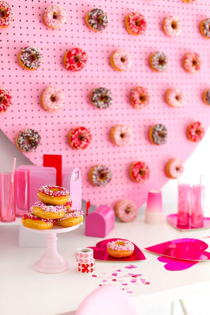 un paneau avec des beignets au chocolat collés des gobelets roses sur une table st valentin originale