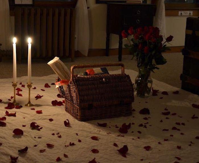 un panier de piquenique sur une couverture au sol avec une vase de roses et deux bougies