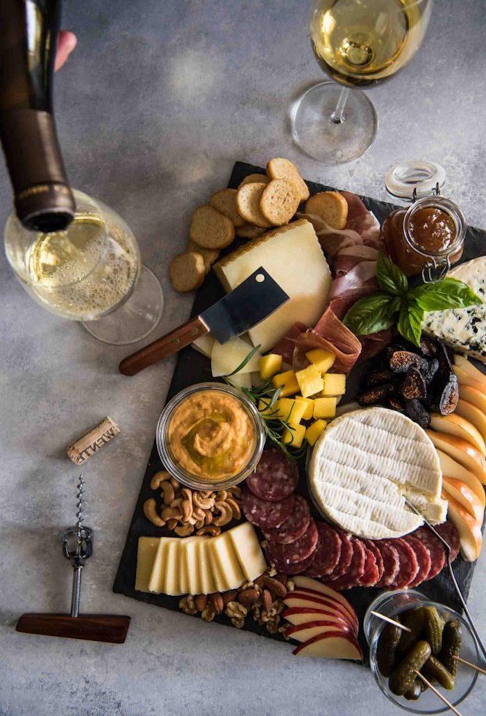 un plateau de charcuterie sur un planche en pierre avec des frommages et deux verres de vin sur une table en marbre