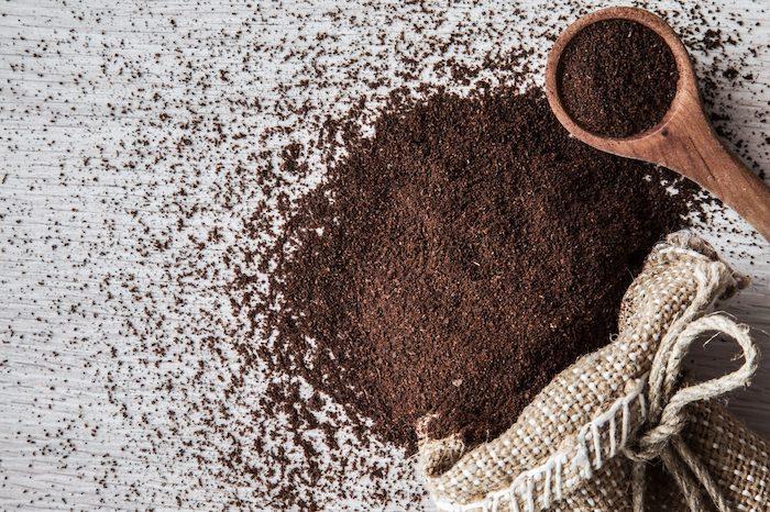 un sac tissé et du marc de café versé sur une table a coté d une cuillère en bois