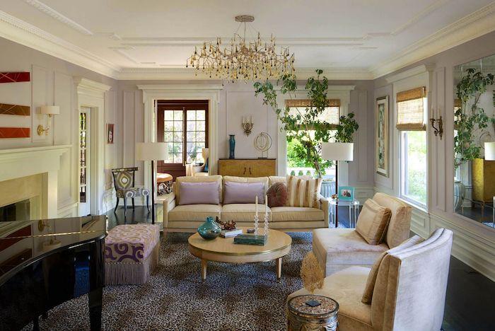 un salon maximaliste avec un tapis animalier une grande plante verte et des canapes beiges avec des coussins roses