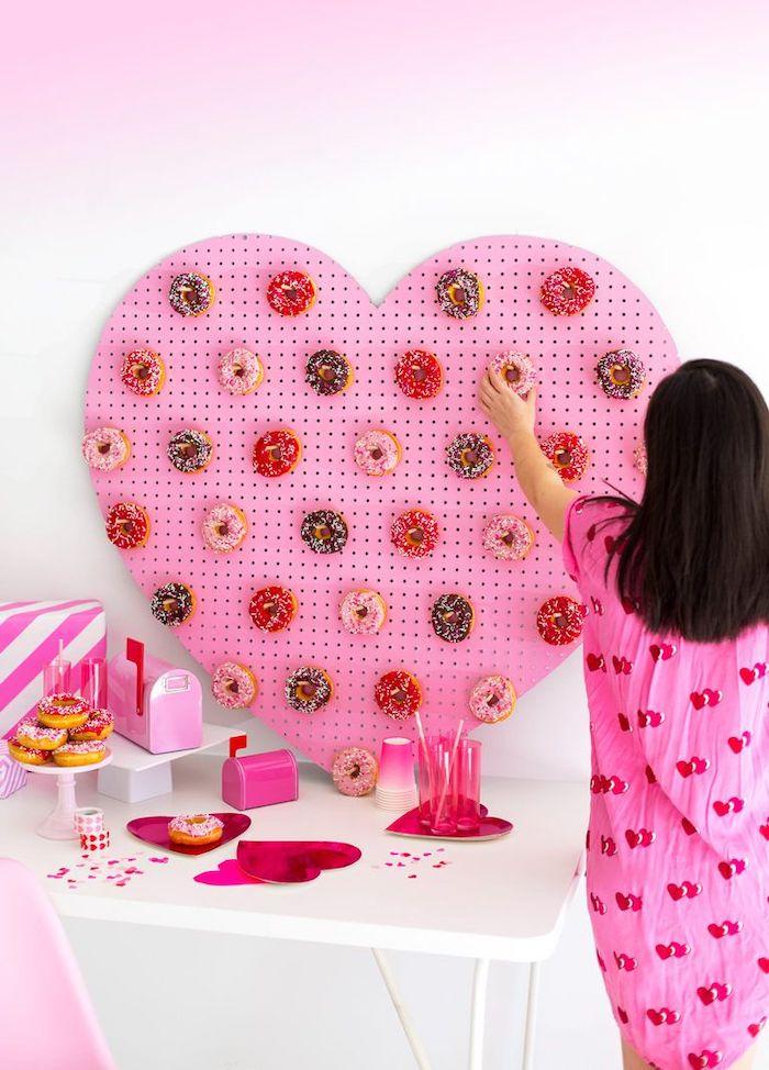 un tableu des beignets en forme de coeur une fille devant saint valentin 2021