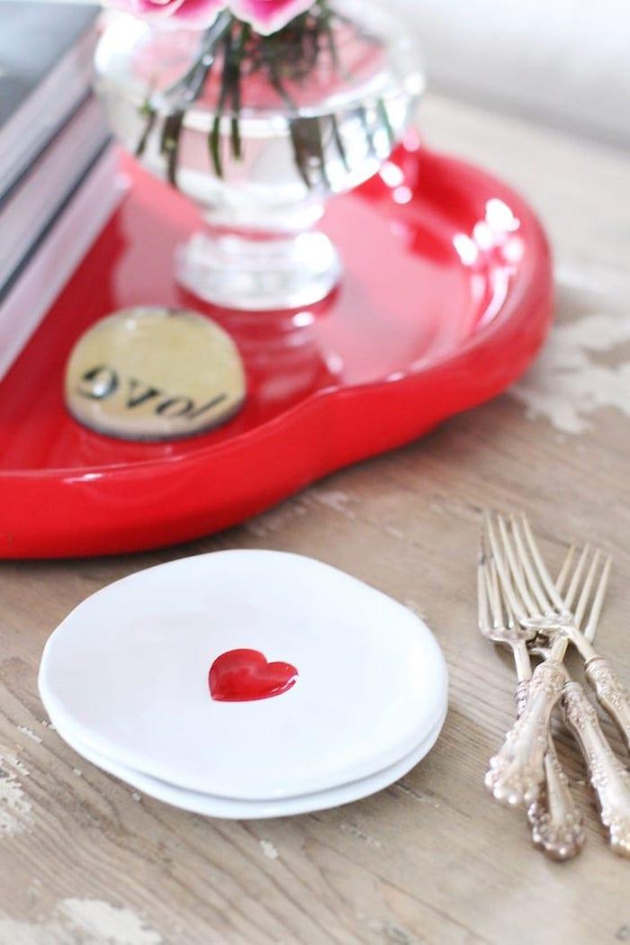 une assiette avec un coeurs déssiné a coté des fourchettes argentines sur la table