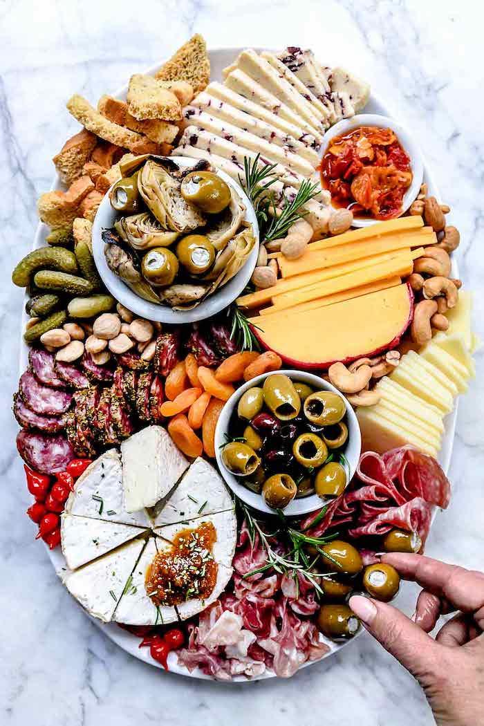 une assiette ovale avec des frommages des charcuteries une table en marbre des fruits secs des cornichons et des olives