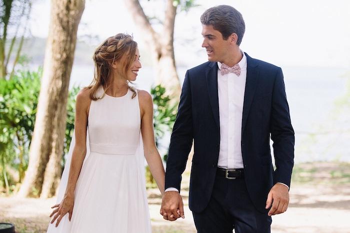 une coupe la journée de mariage femme vetue en robe blanch un homme en cosue bleu marine