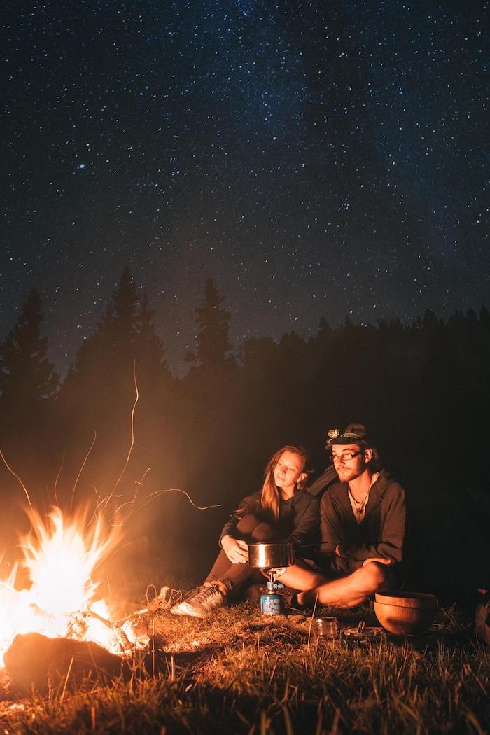 une couple debvant le feu dans la nature des etoiles au ciel quoi faire pour la saint valentin