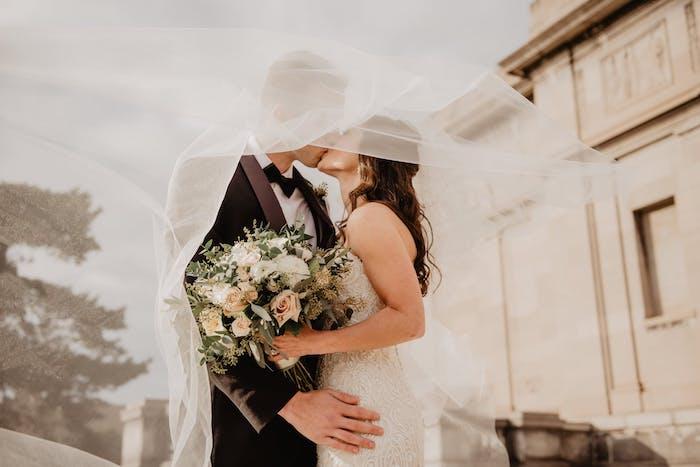 une couple la journée de mariage un grand bouquet des roses blanches et un voile de mariée