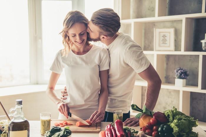 une couple qui fait la cuisine ensemble des legumes sur la table que faire pour saint valentin
