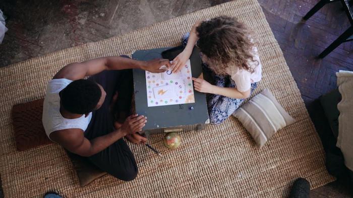 une couple qui joue des jeux de table ensemble pendant la soirée saint valentin une tapis ratane au sol