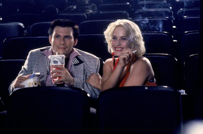 une femme a cheveux blondes et une robe rouge et un homme qui tient un gobelte dans le cinéma