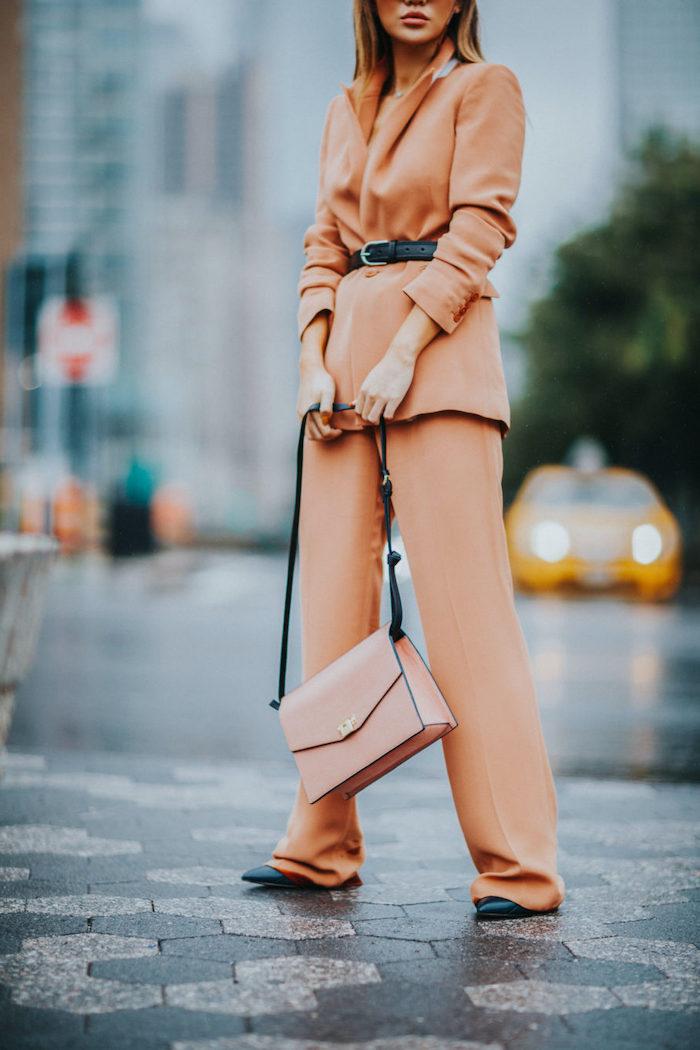 une femme a cote d un grand boulevard vetue en ensemble veste pantalon femme avec une ceinture