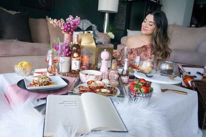 une femme assise devant une table avec des repas abondantes saint valentin celibataire