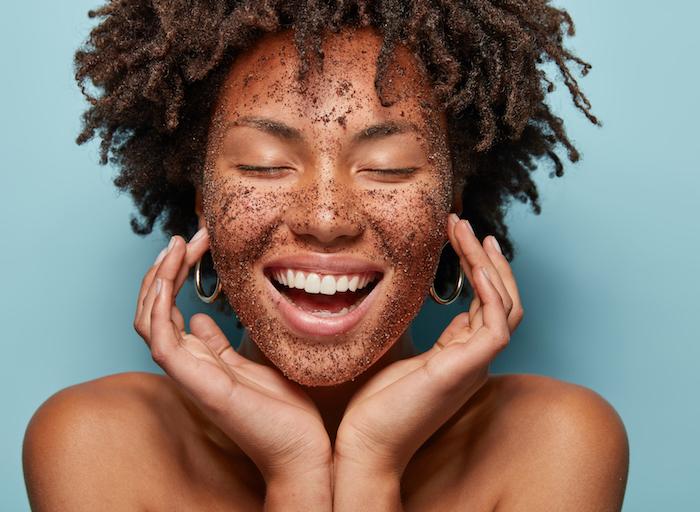 une femme aux cheveux bouclés frotte de gommage de café sur le visage
