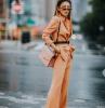 une femme avec des lunettes a soleil modernes un tailleur orange ceinture par la taille et sac en cuir de la meme cuuleur