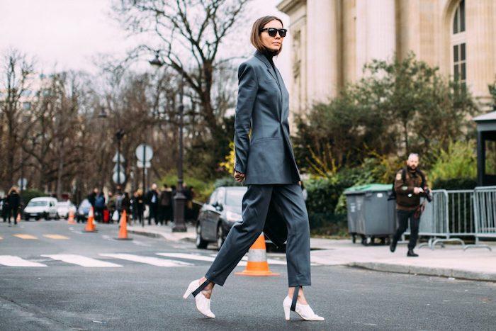 une femme devant le passage pour piétons avec des chaussures a talons blancs et un tailleur gris