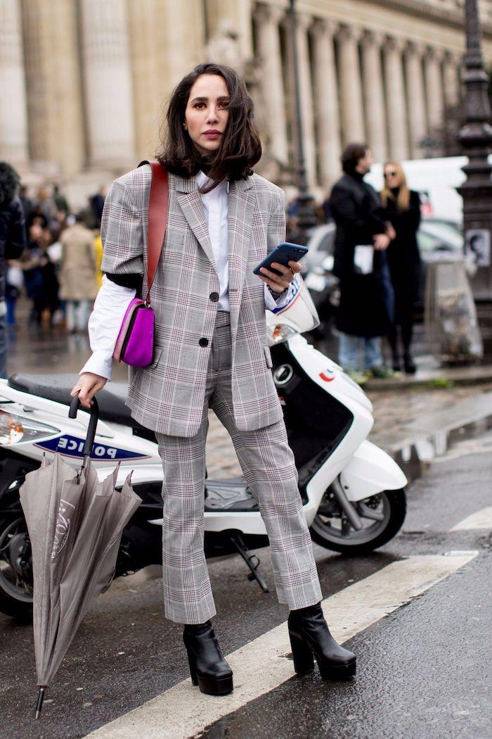 une femme qui tient un parapluie vetue en ensemble tailleur femme chic avec un sac a main rose