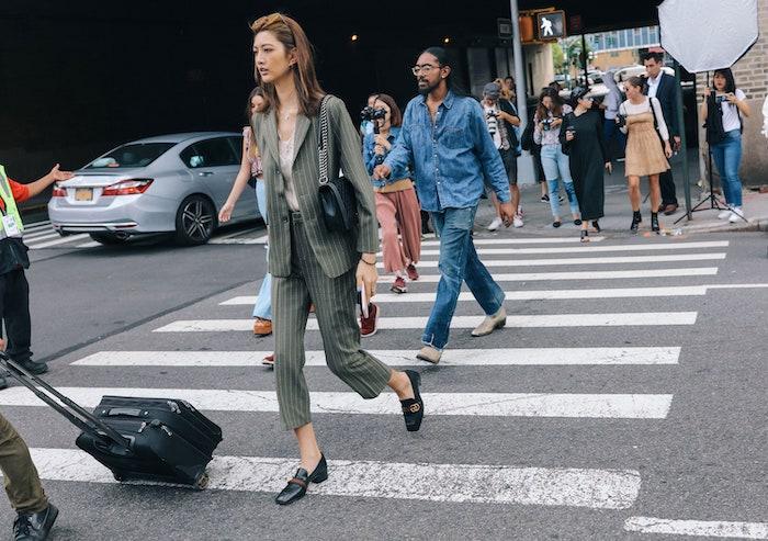 une femme sur le passage cloûté vetue en tailleur reseda aux rayures avec des flaneurs en cuir