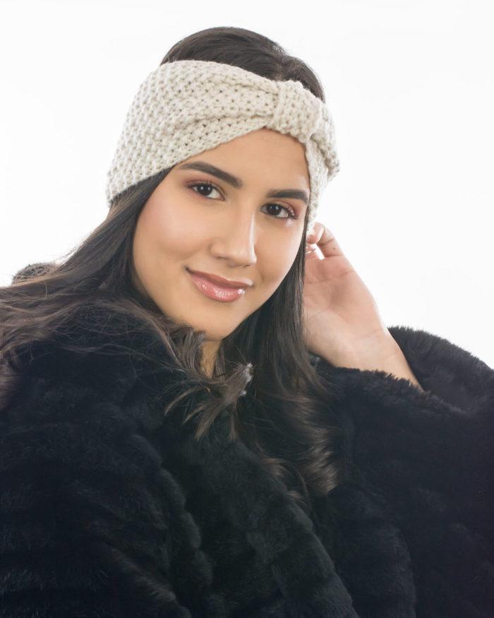 une femme vetue en manteau a fourrure avec un bandeau d hiver tricoté en noeud