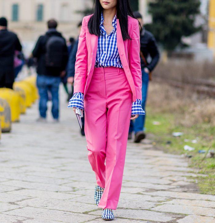une femme vetue en tailleur ensemble rose combine avec un chemisier a carreaux et des chaussures avec les memes motifs