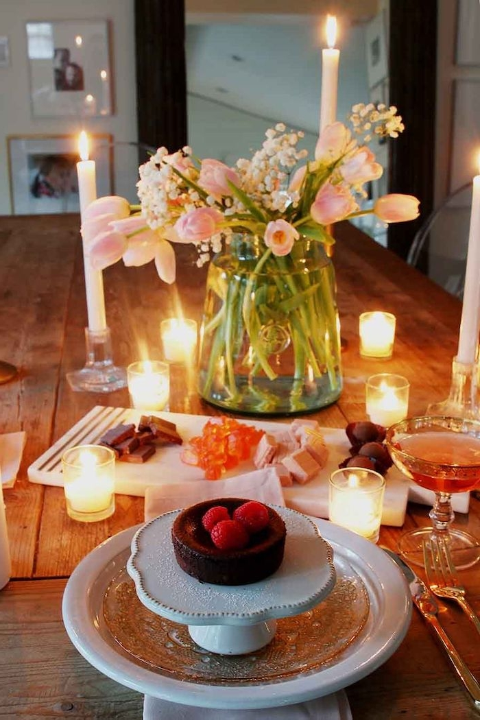 une idée de décorer la table pour saint valentin avec des fleurs roses et des bougies soirée saint-valentin
