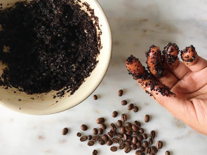 une main avec des taches de marc de café des graines de café sur une surface en marbre