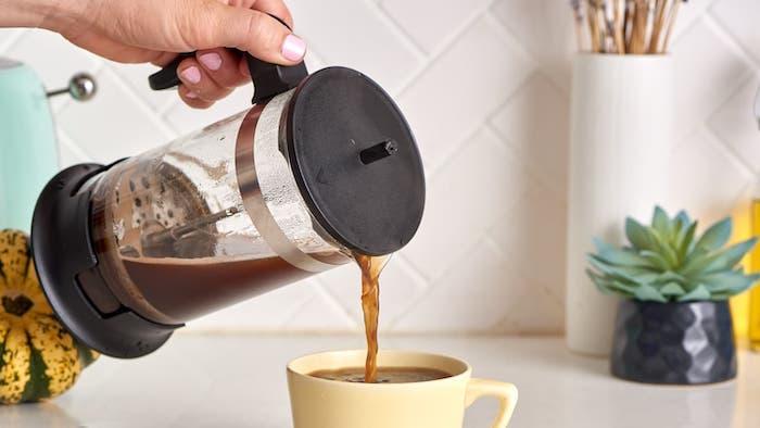 une main qui verse du café dans une tasse jaune sur le comptoir de cuisine