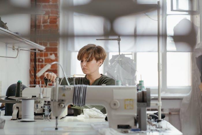 une modiste qui coud dans son atelier sur la machine a coudre