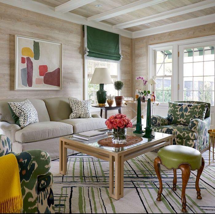 une salle de séjour avec des meubles et détails à motifs en couleurs verte olive et jaune une vase a fleurs roses sur une table en verre