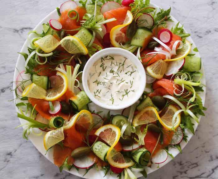 accompagnement saumon fumé avec des légumes et un dip a a la base de frommage servi dans un plateau sur comptoir en marbre