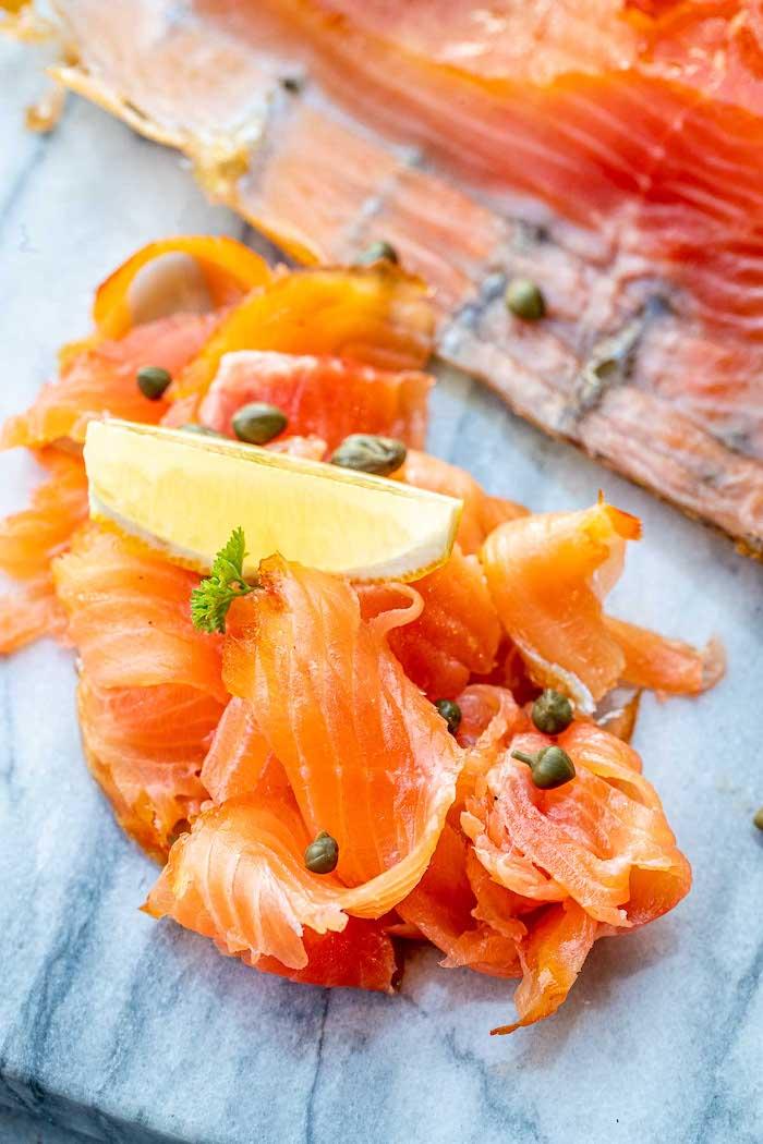 apéro saumon fumé avec des capres et une tranche de citron sur un comptoir en marbre