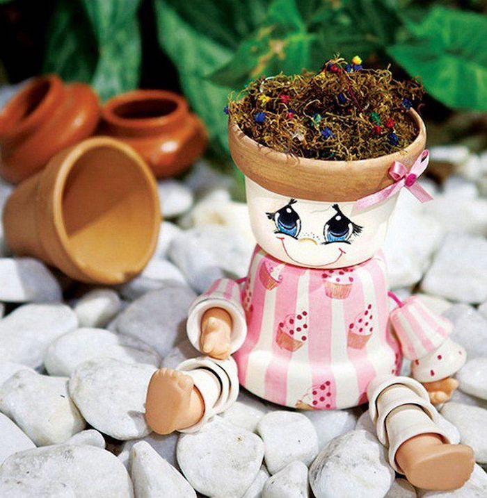 bonhomme en pot de fleur en petites dimensions posé sur des pierres blanches devant des plantes vertes