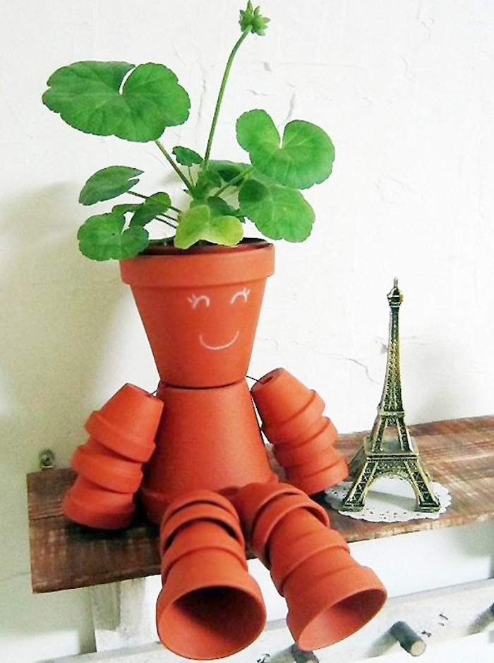 bonhomme en pot de fleur mutliples et attahces pose sur une etagere a coté d une tour eiffel décorative