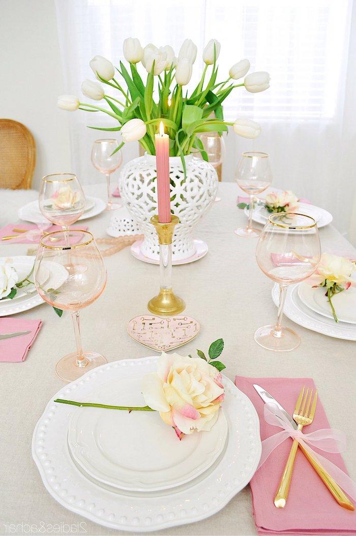 bougie saint valentin en rose une vase aux tulips blancs et une rose jaune dans chaque assiette de la table romantique