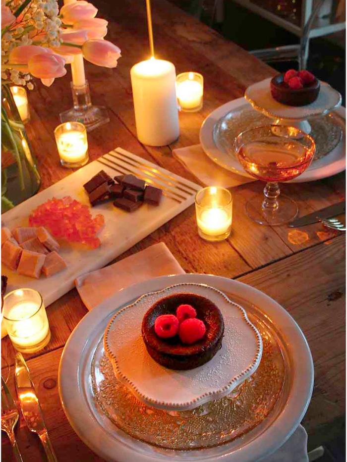 bougie saint valentin sur une table romantique avec des desserts dans des assiettes et des fleurs dans une vase.jpg
