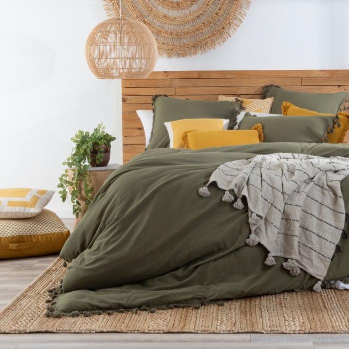 chambre kaki accents linge de lit couverture pompons vert foncé lampadaire rotin suspension murale