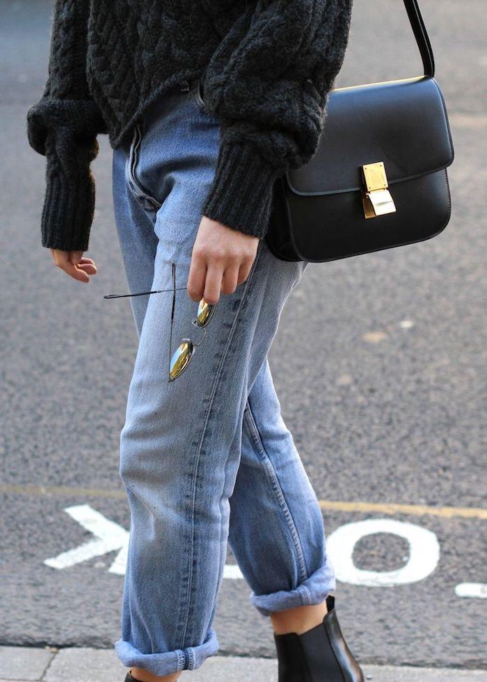 comment porter un jean mom cobinaison avec un pull tricoté et des bottines noires une femme qui tient des lunettes a soleil