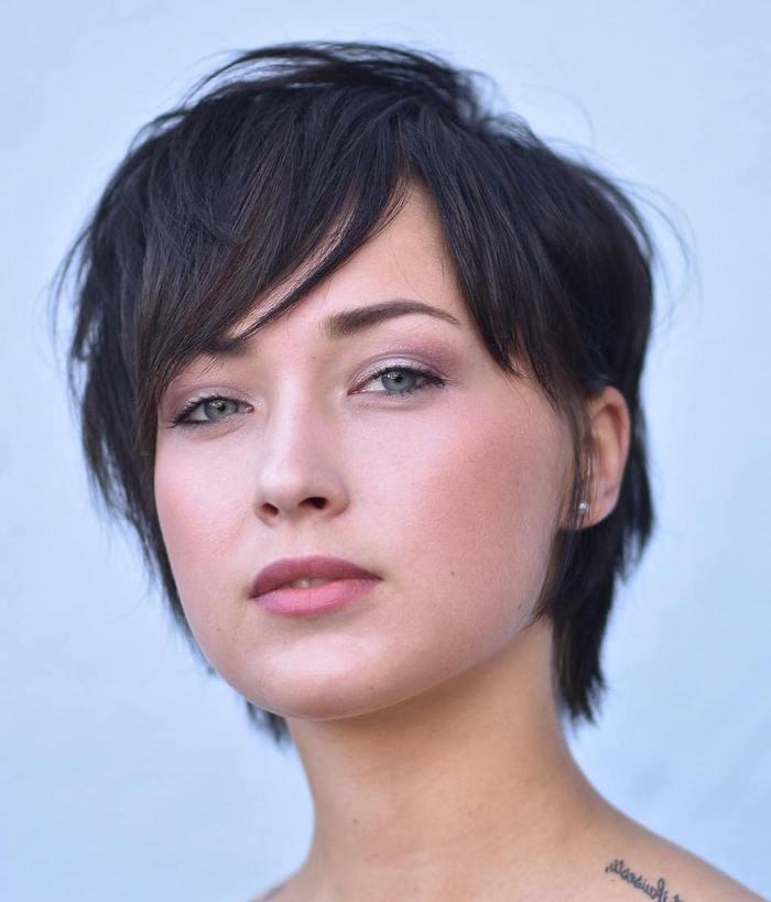 coupe de cheveux frange une femme avec coupe bob courte noire et des yeux bleus