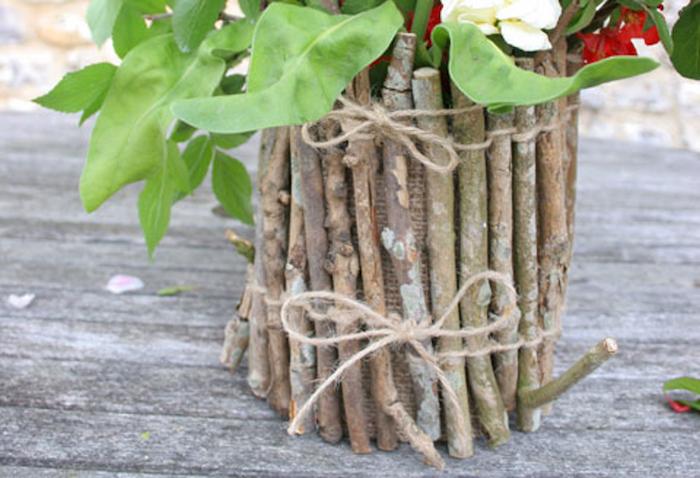 création avec pot de fleur élaboré avec des brindilles et ficelle et tissu de jute sur une surface en bois