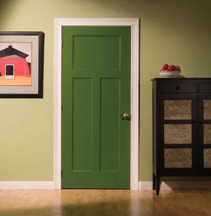 décoration couloiur d entré avec une porte verte dans un cadre blanc entre un tableu et un commode en bois