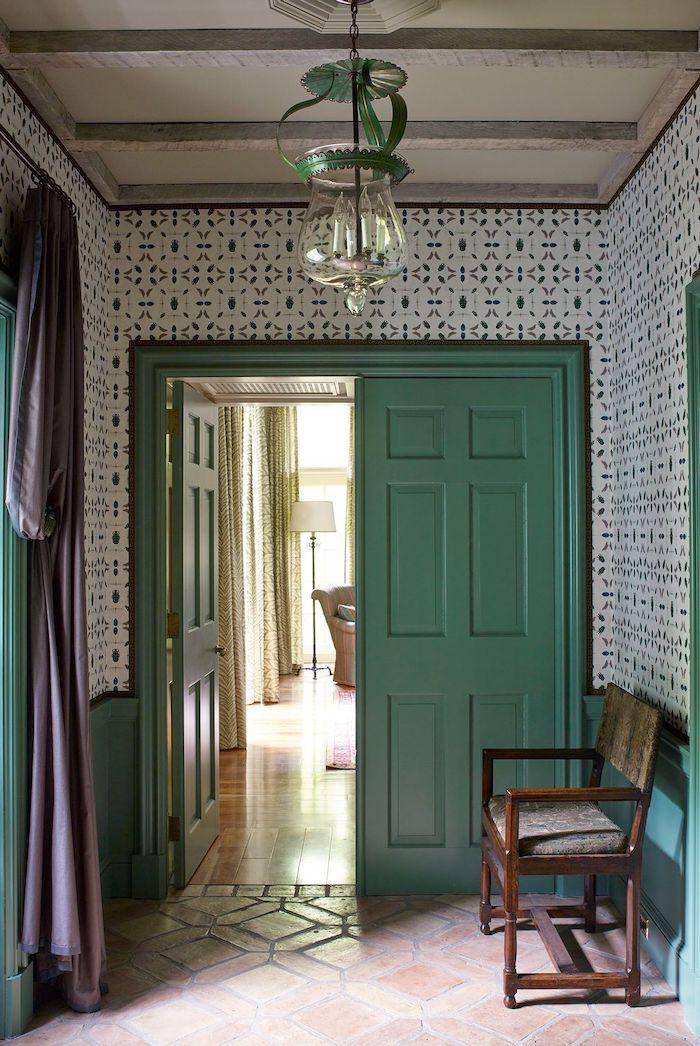 décoration couloiur d entrée avec des papier peint a motifs une porte en vert pastel et un banc en bois