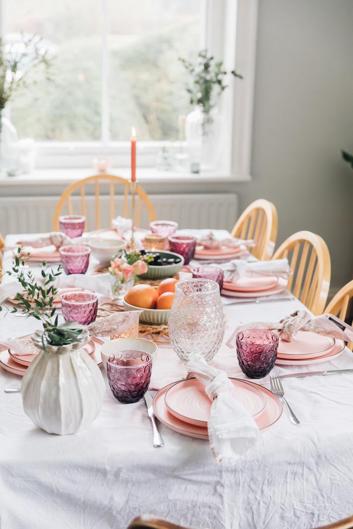 décoration saint valentin avec des assiettes et verres roses une bougie rouge allumée et es oranges