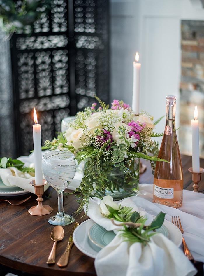 deco centre de table a l aide de fausse verdure des couverts et porte bougies en cuivre une boutelle de vin ouverte