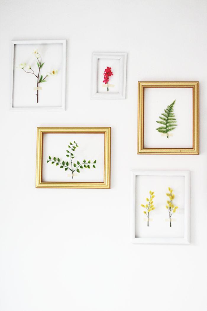 deco murale tendance pour printemps salon cadres en blanc et or avec des branches de fleurs à l intérieur mur blanc décoré