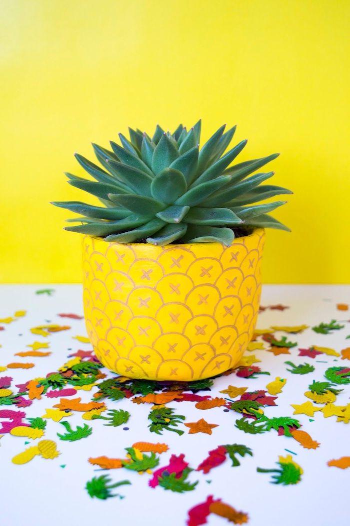 deco pot de fleur un succulent dans pot décoré a motifs d ananas posé sur une table avec des confettis parsemées