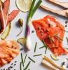 des differentes parties de saumon fumé avec des légumes et des herbes sur une surface blanche