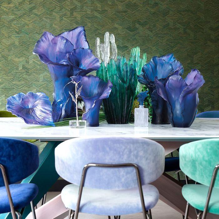 des vases cristaux daum sur une tqble blqnche derrierre des chaises en plastique