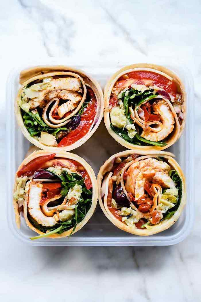 des wraps coupes en troncs et rangés dans une boite en plastique idée de déjeuner au bureau