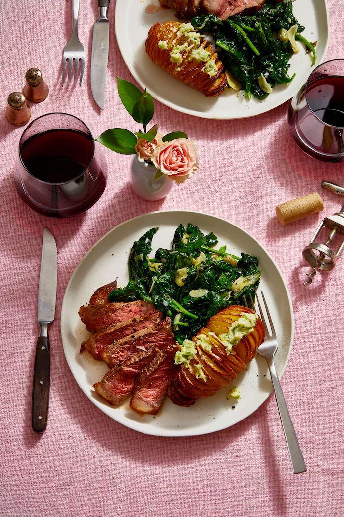 diner au chandelle pour saint valentin avec deux verres de vin rouge et deux portions de patates et epinards