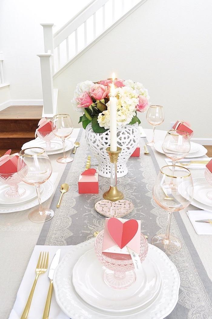 diner au chandelle une table décoré des fleurs un chemin en tissu et des petites cartes dans les assiettes