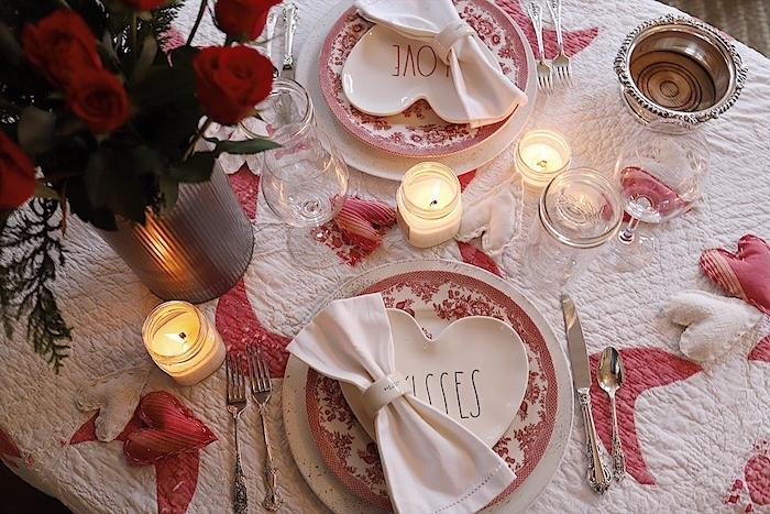 diner aux chandelles sur une nappe blanche décorée de petits coeurs en tissu en une vase aux roses rouges